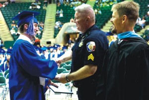 POMP AND PRIDE - Decatur Police Sgt. Darrell Hicks beams after seeing his son Sterling walk across the graduation stage Thursday in Denton. Messenger photo by Joe Duty