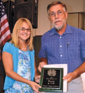 FRIEND OF 4-H - Michaela Martin presents Gary Markum of Tractor Supply Co. in Decatur with the Friend of 4-H Award.