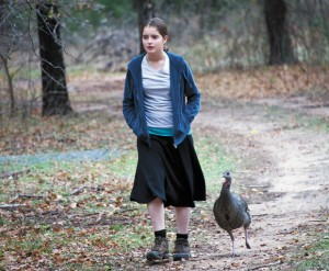 TURKEY TROT - Palamia Davis, 12, of Irving is followed by one of the turkeys she helped save last year after it got ran over by a lawnmower on her family's farmland in northern Wise County. Messenger photo by Joe Duty