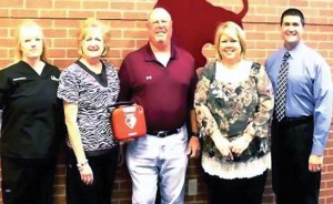 AED DONATION - Susanne Boston (left) and Robert Stapp (far right) of North Texas Sport and Spine present a new automated external defibrillator (AED) to Bridgeport High School recently as school nurse Linda Green, athletic trainer Billy Newsom and Principal Jaime Sturdivant accept for the school. Submitted photo
