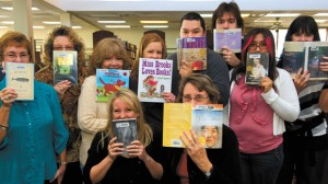 PEEKING AT SUCCESS - The Decatur Public Library staff can't hide their excitement about being named runner-up Best Small Library in America by Library Journal and the Bill and Melinda Gates Foundation. From left (back row) are Sharon Herzberg, Linda Meador, Maria Zamora, Abby Dozier, Cisco Perez, Chris Shenkir, Denice Herrera, Becky Gamm, (front) Cecilia Barham and Suzzie Hubble. Not pictured is John Winfrey. Messenger photo by Joe Duty