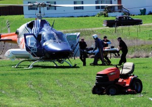 CRITICAL LIFTOFF - Medics wheel a 4-year-old boy critically injured in a lawn mower accident to a CareFlite helicopter waiting to carry him to Cook Children's Hospital in Fort Worth. The boy suffered serious lacerations to his left leg and stomach. Messenger photo by Joe Duty