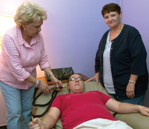 """BEAMS OF ELIMINATION - Donna Jones (left) and Debbie Smith focus cold, low-level laser beams on """"energy points"""" on a stand-in patient, Amanda Moore. The sister duo will host a grand opening Monday for their joint venture - Wise Laser Therapy. Messenger photo by Joe Duty"""