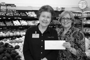 HELPING THE HUNGRY - Market Place employee Odessa Presson (left) is presented with a cash prize for outstanding contribution to the fund-raising effort by co-owner Margie Shelton.