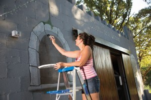 ART RETRO - Sabrina Polk, a Bridgeport artist, puts the final touches on the newest cabin at Wise County Old Settlers' Reunion. The cabin, built by Will and Keely Gage, of Paradise, mimics a medieval castle. Messenger photo by Joe Duty