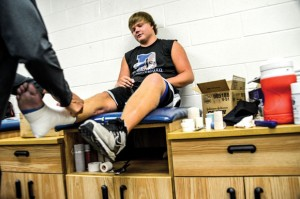 PREPARING FOR WORK - Trainer Kurt Wood wraps Tyler Story&#039;s foot and ankle before a workout Thursday. The tape, along with a brace, allows the senior to run on his right leg despite a dead nerve that keeps him from lifting his foot. Messenger photo by Joe Duty