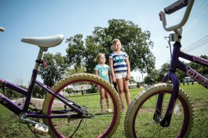 CHILDREN NOT AT PLAY - Ashlyn Arnold, 5, and Britney Arnold, 9, have little to do at Delora Doughty Royal Park in Newark besides ride their bicycles in circles ever since the city removed the dilapidated playground equipment three years ago and never replaced it. Messenger photo by Joe Duty