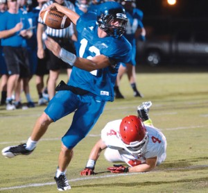 SLIPPING AWAY - Decatur quarterback Grayson Muehlstein runs away from a Mineral Wells tackler during the Eagles' scrimmage Friday. Messenger photo by Mack Thweatt