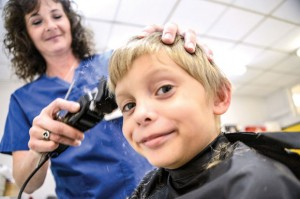TIME FOR A TRIM - Volunteer Debbie Cross gives 8-year-old Waylon York a haircut at Thursday's Back to School Night at Slidell ISD. In addition to haircuts, students and parents also received health, nutrition, eye and dental care information. Messenger photo by Joe Duty