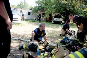 TIRING EFFORT - Firefighters try to catch their breath after fighting a blaze in a mobile home in Newark Sunday afternoon. Messenger photo by Joe Duty