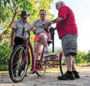 UNSTOPPABLE - Charlie Young and Bill Silver, members of AMBUCS service organization, Thursday present Jessica McClure of Greenwood with an AmTryke, a modified tricycle that accommodates riders of all ages, sizes and physical limitations. McClure has cerebral palsy with dystonia. Messenger photo by Joe Duty