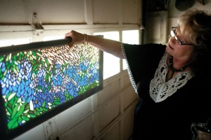 BLUEBONNETS - Totty shows one of her larger mosaic pieces. She lined up small pieces of glass to create a bluebonnet scene. Messenger photo by Jimmy Alford