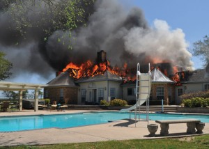 FIRE-WATER - A large country home located between Greenwood and Slidell caught fire Sunday afternoon. The blaze spread quickly throughout most of the home. Above is a poolside view of the destruction. Messenger photo by Brandon Evans
