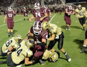 GANG TACKLE - Alvord's Ty Silvey (9), Brandon Aeling (28) and Shane McKinney (34) combine to bring down a Bowie runner. Messenger photo by Mack Thweatt