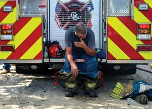 GETTING RELIEF - Slidell/Greenwood firefighter Rodney Yard tries to catch his breath after being overcome by the heat and smoke while fighting Thursday's blaze. Messenger photo by Joe Duty