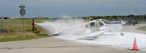 Decatur firefighters spray down fuel leaking from the downed plane with foam. Photo by Joe Duty.