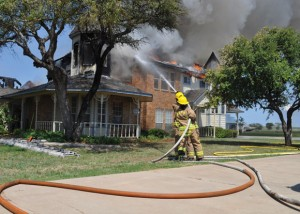WRECKED RENOVATION - Firefighters from six departments battled tirelessly for almost seven hours in 99-degree heat as a 3,500-square-foot home burned on the prairie. The owner was in the process of renovating the 26-year-old house. Messenger photo by Brandon Evans