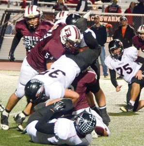 IN THE TRENCHES - Bull defenders Hagen Davis (54) and Jessie Smith (8) up-end Argyle runningback Terry Moore in Friday night's playoff game in Flower Mound. Messenger photo by Mack Thweatt
