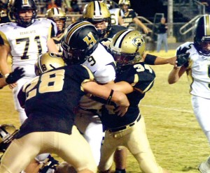 SANDWICHED - Alvord's Brandon Aeling and Shane McKinney team up to crunch a Henrietta runner in the 12-10 Bulldog win Friday. Messenger photo by Mack Thweatt