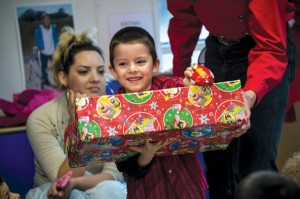 ALL SMILES - Rosendo Fernandez Jr. of Decatur receives a box of gifts donated by local 4-H members and their families with a grin. The gift boxes contained a set of clothes, shoes, toiletries and toys donated by 4-H members and their families. Messenger photo by Joe Duty