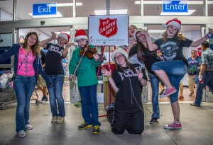 RINGING THE BELL - Thomas Lynch, 14, of Alvord entertained Wal-Mart shoppers by playing Christmas carols on his fiddle Monday night while he and Alvord FCCLA members rang the bell for The Salvation Army. Also pictured are (from left) Esther Ruiz, Mikena Mader, Lynch, Emily Hacker, Reagan Guthrie, Sarah Nichols and Makayla Deweber. Messenger photo by Joe Duty