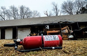 AFTERMATH - An empty fire extinguisher sits on the lawn outside the Eighter from Decatur apartments. Fire ravaged one of the buildings at the complex Sunday night, leaving three units gutted, one with heavy damage and three others with heavy smoke damage, according to Decatur Fire Chief Mike Richardson. Messenger photo by Joe Duty