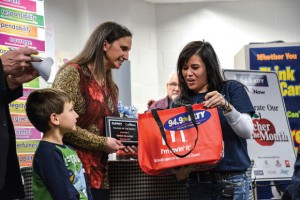 GOODY BAG - Eva Royer, KLTY senior account executive, presents Gwen Hilliard with her bag of prizes during Monday's presentation in her classroom at Northwest High School. Looking on in the background is Hilliard's father, Arnold Jochim. Messenger photo by Joe Duty