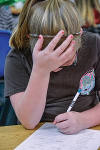 GROUPED TOGETHER - Teachers and administrators say CSCOPE stresses more group work and lessons that require higher-level thinking than past curriculums. Boyd fifth-grader Lindsay Carroll scratches her head while solving math problems. Messenger photo by Joe Duty