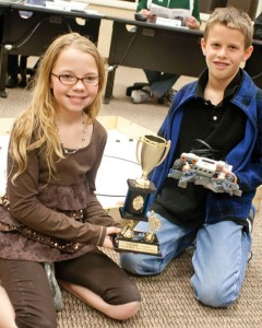 HELLO MR. ROBOTO - Lynsey Medlin (left) and Matthew Eisen pose with their team's robot and second place trophy at Monday night's board meeting. A third teammate, Kyndel Beck, was unable to attend. Messenger photo by Jimmy Alford