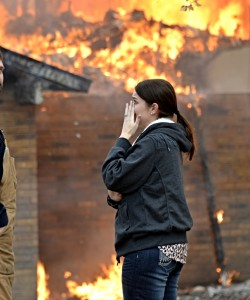 Ashly Dobyns can only watch as fire consumes her family's home Wednesday morning. Photo by Joe Duty.