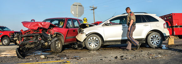 LOW VISIBILITY - Limited visibility due to a line of 18-wheelers parked alongside the road might have caused two SUVs to collide at the intersection of Farm Roads 51 and 2123 Tuesday morning. Both drivers were taken to a local hospital with minor injuries. Messenger photo by Joe Duty