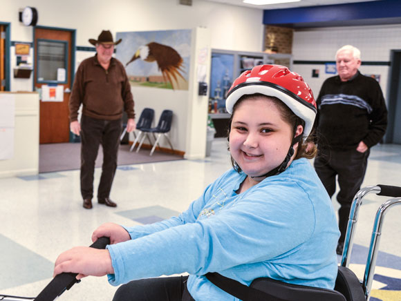 MOVING GIFT - After school last Friday, Charlie Young and Bill Silver (background left to right), members of AMBUCS Inc. service organization, presented McCarroll Middle School seventh grader Aneliz Medina an AmTryke, a modified tricycle that accommodates riders of all ages, sizes and physical limitations. The provides a fun form of therapy for the 14-year-old, who is recovering from a stroke. Messenger photo by Joe Duty