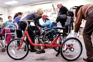 NEW SET OF WHEELS - Physical therapist Sheri Huling helps McCarroll Middle School seventh grader Aneliz Medina from her wheelchair to her new AmTryke, with the help of Bob Silver of AMBUCS, the organization that donated the tricycle. Aneliz's mother, Alma, and 10-year-old sister, Paola, are also pictured. Messenger photo by Joe Duty