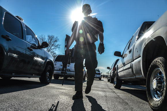 PEACEFUL FINISH - Jason McCall, a member of the Wise County Sheriff's Office SWAT team, patrols an area near after a standoff that lasted for a couple hours at a home near the Bridgeport Municipal Airport. Messenger photo by Joe Duty