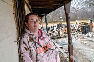 PICKING UP THE PIECES - Amanda Strine stands outside of her apartment Tuesday morning as she returned to see what she could salvage. Her apartment was among those damaged by Sunday's fire. Messenger photo by Joe Duty