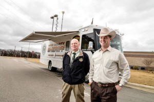 READY TO ROLL - Captain Kevin Benton (left) and Sheriff David Walker stand outside the county's new mobile command post parked in front of the Sheriff's Office last week. The state-of-the-art vehicle will be used as a communication base at the site of extended emergencies. Messenger photo by Joe Duty