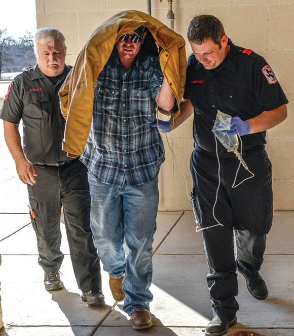 TAKEN AWAY - Jimmy Warden, 43, of Bridgeport, is taken to the emergency room at North Texas Community Hospital in Bridgeport after he turned himself over to authorities for allegedly making a terroristic threat and aggravated assault and creating a standoff situation. Messenger photo by Joe Duty