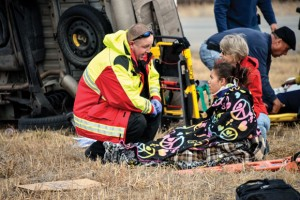 TENDING TO TRAGEDY - Wise County medic Randall Preuninger tends to Tina Gillium, 21, of Colorado Springs, Colo., injured in Friday morning's wreck where six people were ejected from the wrecked van. Messenger photo by Joe Duty