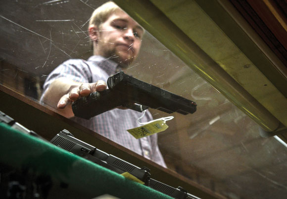 UNDER FIRE - Like many other stores, 2K Pawn and Gun Shop in Decatur has had trouble keeping ammunition on the shelves due to high demand. They've also seen an increase in people, especially women, purchasing handguns lately. Employee Ty McMaster displays a model. Messenger photo by Joe Duty