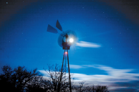 BLOWING IN THE WIND - A windmill at TADRA Point spins furiously in the heavy, early morning wind. Behind, the full moon shines brightly, illuminating the clouds. Messenger photo by Jimmy Alford