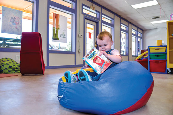 COZY CONFINES - Young Emilee Greeson looks at a book in the comfort of a bean bag chair inside the newly-remodeled Chico Public Library Tuesday. The front of the building received a new paint job and windows late last year and an extensive interior renovation last summer. Messenger photo by Joe Duty