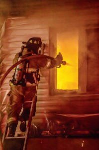 DIRECT ATTACK - An Alvord firefighter sprays water through a second-story window at a fire at a duplex near downtown Alvord Tuesday night. No one was injured in the blaze. Messenger photo by Joe Duty