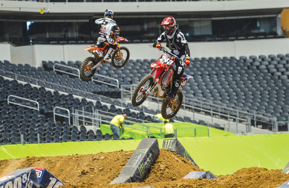 FLYING HIGH - Mitchell Oldenburg (right) takes his practice laps at Cowboy's Stadium in Arlington Thursday in preparation for Saturday's race. Messenger photo by Joe Duty