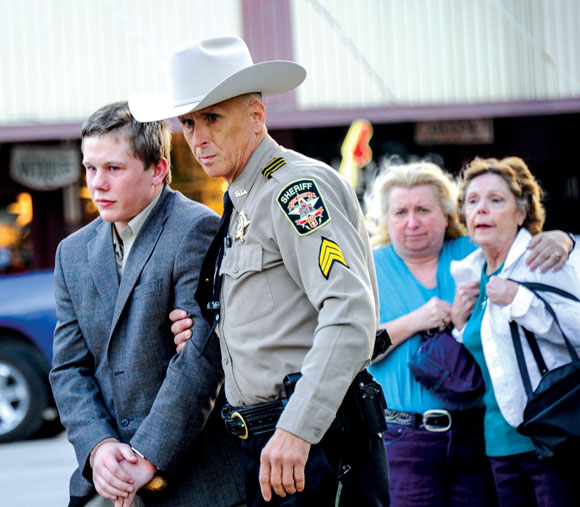LONG WALK - Distraught family members of Danny Nalley watch as Sgt. Cavin Riggs with the Wise County Sheriff's Office leads the 19-year-old from the courthouse in Decatur Thursday evening. He had just been sentenced to two years in state jail for criminally negligent homicide. Messenger photo by Joe Duty