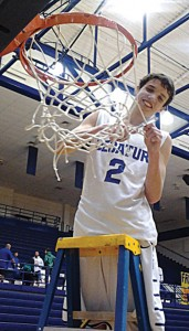 NICE FINISH - Decatur's Phillip Walker helps cut down the net after the Eagles district championship clinching win over Krum. Messenger photo by Jimmy Alford