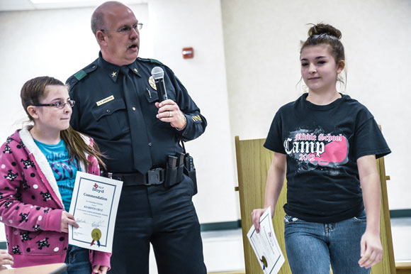ONE GOOD TURN - Boyd Police Chief Greg Arrington commends sisters Kearstin Cruz, 11, and Celeste Cruz, 13, for their model behavior at a function for the girls at Boyd Middle School last Friday. The sisters found a wallet in a parking containing almost $1,400 in cash and immediately turned it over to the proper authorities. Messenger photo by Joe Duty
