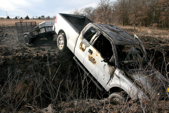SUDDEN STOP - A pickup pulling a stolen trailer, driven by Shannon Hood, took a nose-dive into a ravine Sunday. The pickup caught fire, which spread to the grass and two patrol vehicles. Messenger photo by Joe Duty