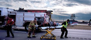 UP IN THE AIR - Emergency responders prep Larry Givens, 69, of Dallas, for transport in a helicopter bound for John Peter Smith Hospital Monday. Messenger photo by Jimmy Alford