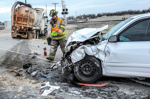 WRECK SCENE - A firefighter surveys the damage following an accident at Texas 114 and County Road 3241 near Paradise Monday morning. Toby Baker, who was driving the white Hyundai Elantra, later died at Wise Regional Health System in Decatur. Messenger photo by Joe Duty