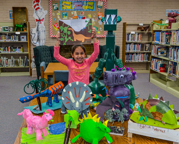 DINO DISPLAY - Bridgeport Elementary second grader Montserrat Uribe-Baeza shows a dinosaur she made from recycled products. The creations of 122 students are on display at the Bridgeport Public Library through next week, which is when the library will hold its used books sale. Messenger photo by Joe Duty